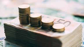 euro coins on cash stack closeup PZVVPKH